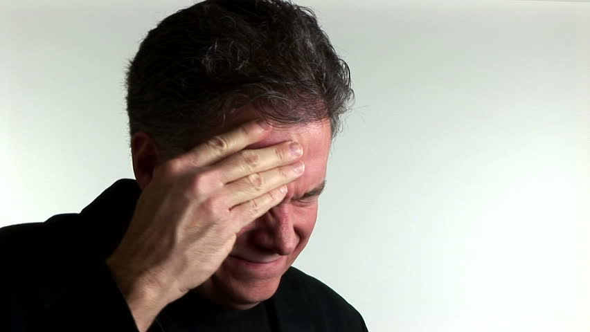 A man suffering from a migraine headache stops and looks at the camera. - HD stock video clip
