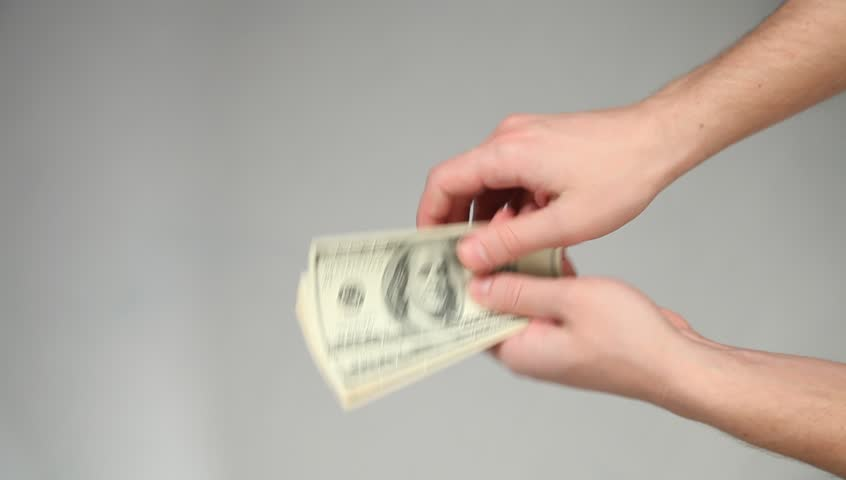 Hands giving and taking dollars on grey background - HD stock footage clip
