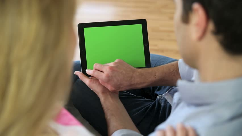 Couple looking at pictures on electronic tablet