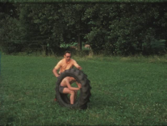Vintage 8mm film: Boy in tire rolled by father, 1970s