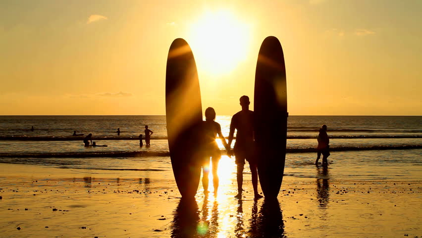 Surfer couple in silhouette holding long surf boards at sunset on tropical beach - HD stock footage clip