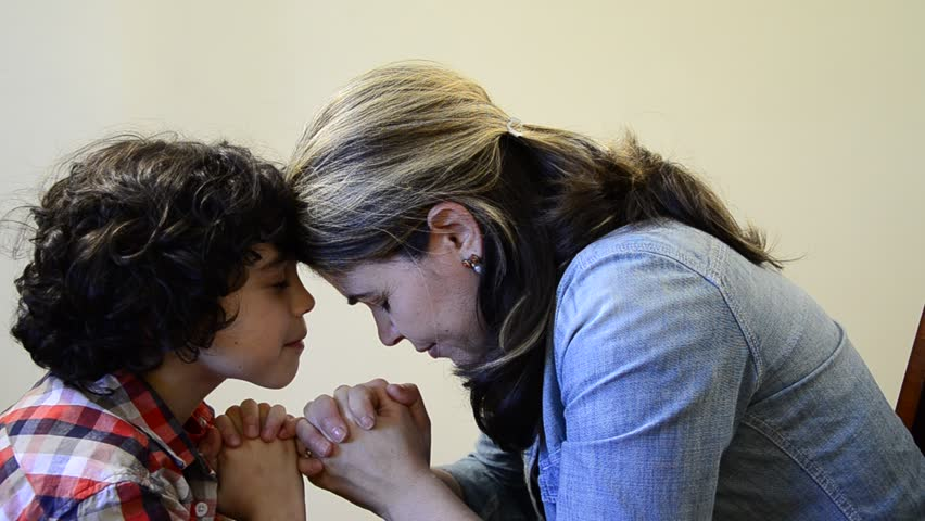 Hispanic mother and son praying together