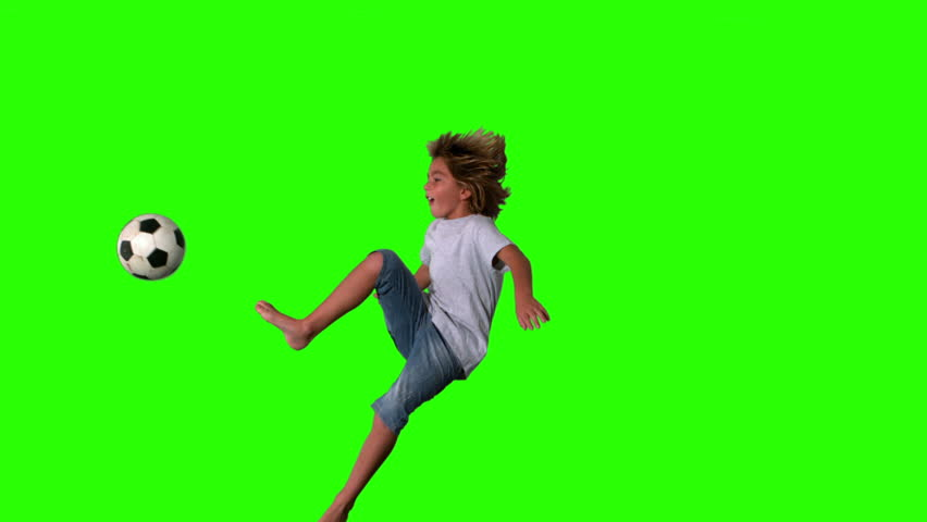 Boy jumping and kicking football on green screen in slow motion