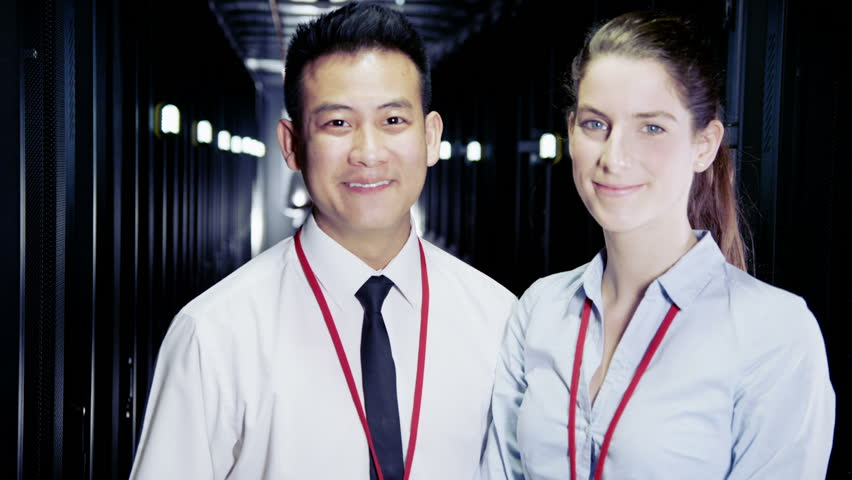 Two people of mixed ethnicity are working in a data center with rows of server racks and super computers. They are walking up and down and checking all of the equipment.