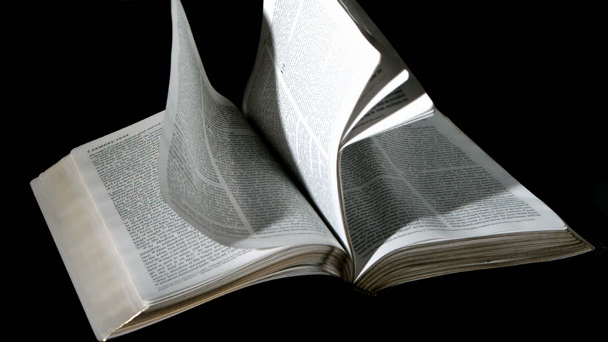 Bible pages turning in the wind on black background in slow motion - HD stock video clip