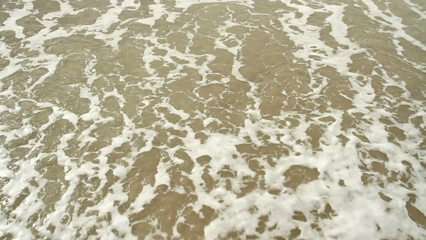 Tidewash Loop. Sea tide washes up a sandy shore and out again.  Loop-able clip.
