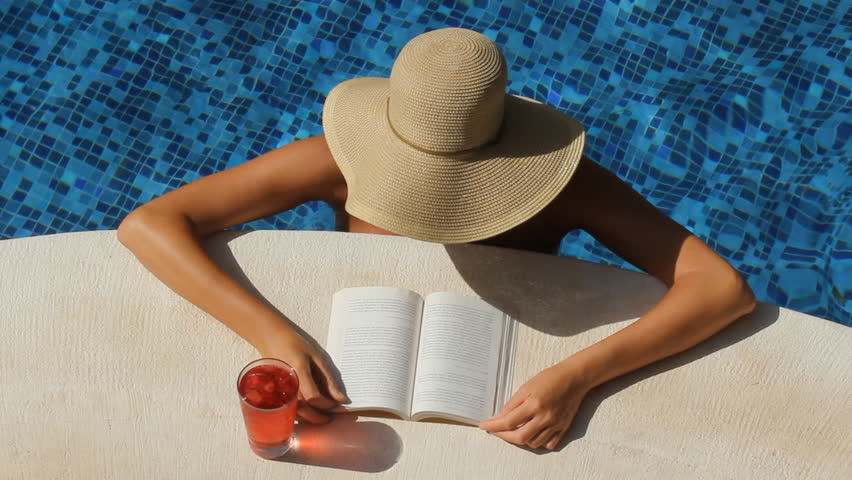 Woman with wide brimmed hat reads by the side of a pool. Tulum, Mexico.