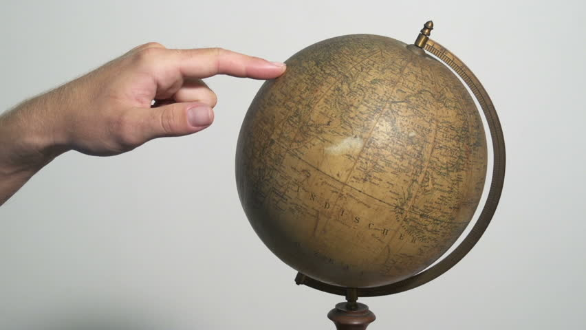 Man spinning a globe and pointing on it