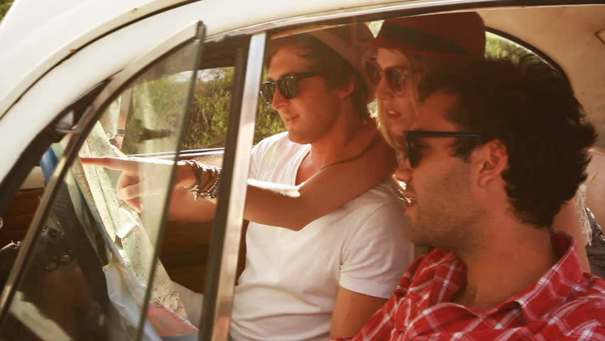 Young Hipster friends on a roadtrip looking at a map.