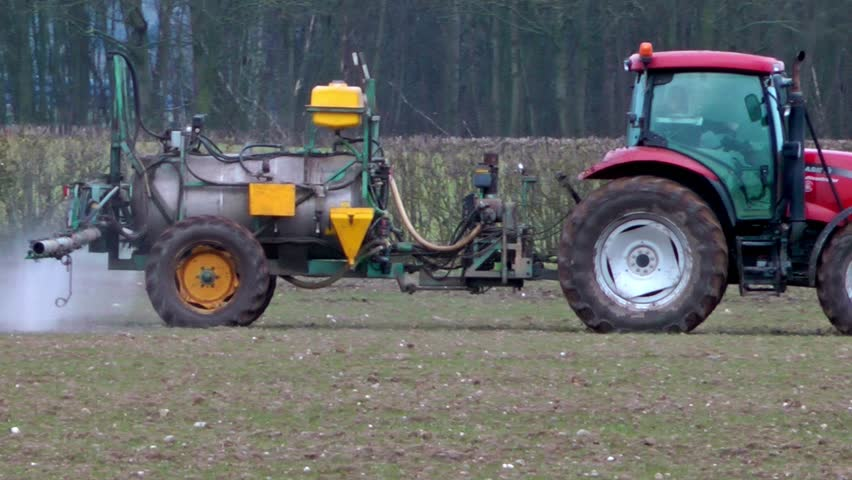 Tractor Spraying Fertilizer Onto A Crop Of Winter Wheat (Staffordshire,UK - March 2013)