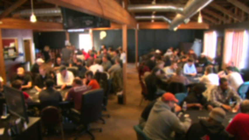Soft focus, unrecognizable people in poker club gambling at poker card tables, time lapse.