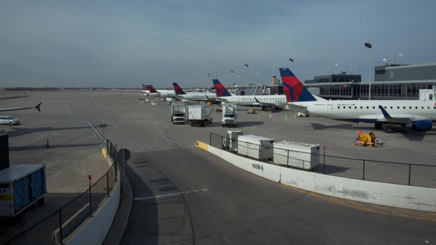 Minneapolis - Circa 2012: Time-lapse of Jet airliners and service trucks arriving and departing outside the terminal