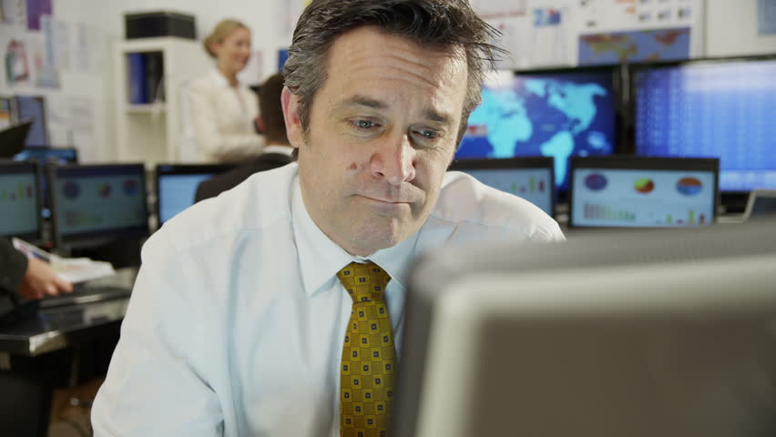 Confident and mature stock market trader is doing a deal over the phone in a busy office filled with computers. The rest of his team are hard at work in the background. In slow motion.
