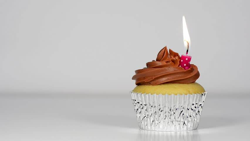 Delicious Vanilla Cupcake with Chocolate Frosting and Burning Birthday Candle