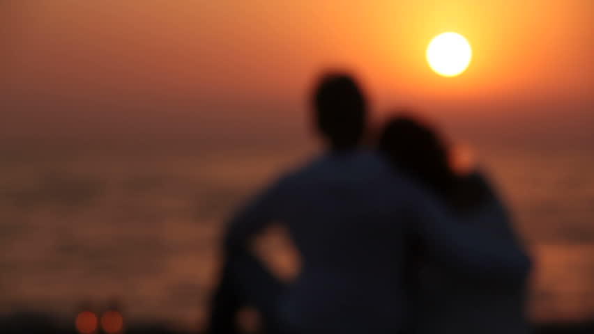 Romantic couple is enjoying sunset sitting on the beach and hugging first defocused, then focused