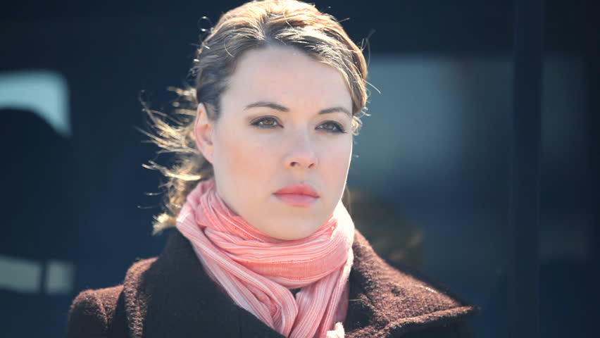 Close Up Portrait Of A Blond Young Woman Wearing A Pink Scarf And Winter Coat Outdoors In Cold Weather