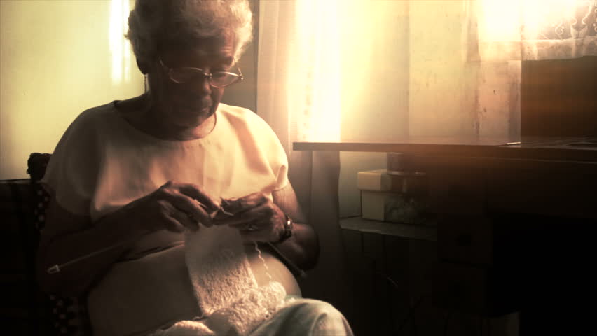 Older woman knitting a scarf with needles at home