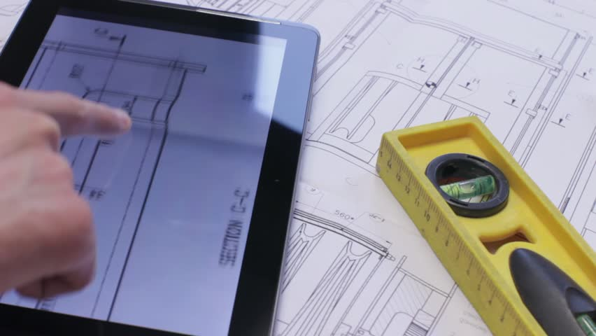 Engineer using Tablet PC while working with Blueprints.