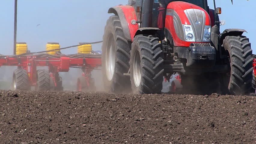 Agricultural tractor sowing and cultivating field