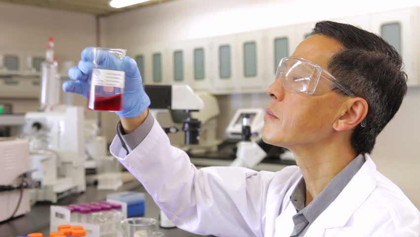 Scientist in laboratory examining liquid in glass beaker. Shot on Canon 5d Mk2 with a frame rate of 30fps - HD stock footage clip