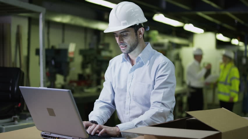 A young male warehouse employee, wearing a hard hat is working on a laptop computer and checking his stock.