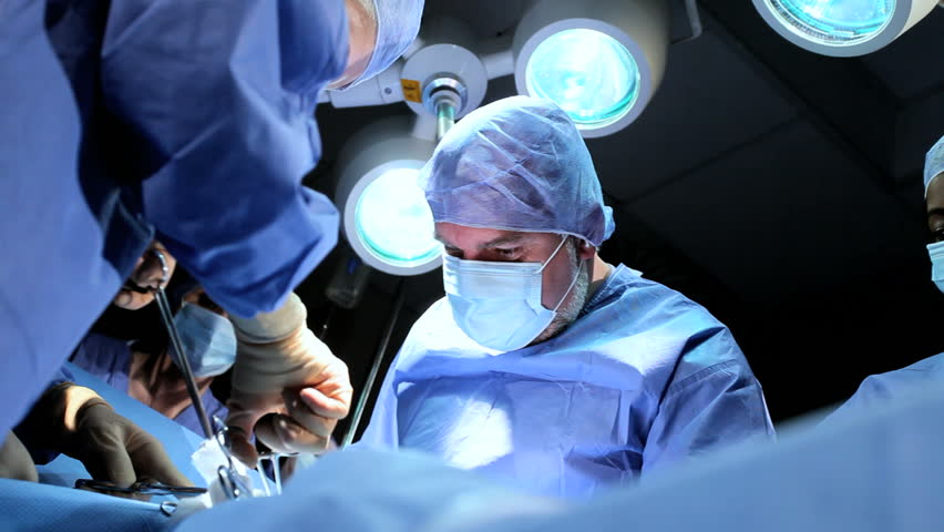 Doctor wearing protective clothing performing surgery using sterilised equipment