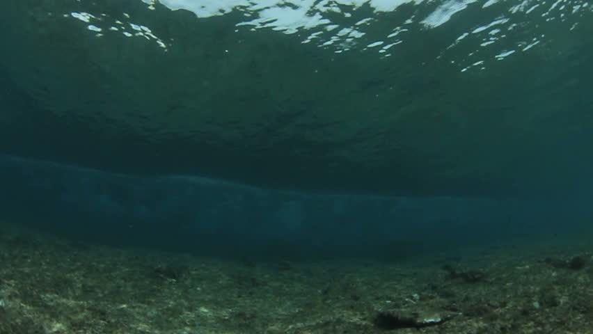 Underwater ocean wave breaking in crystal clear water