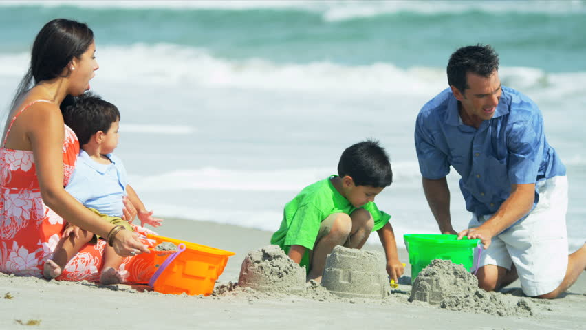 Little Latin American kids building sand castles together with parents on beach shot on RED EPIC - HD stock video clip