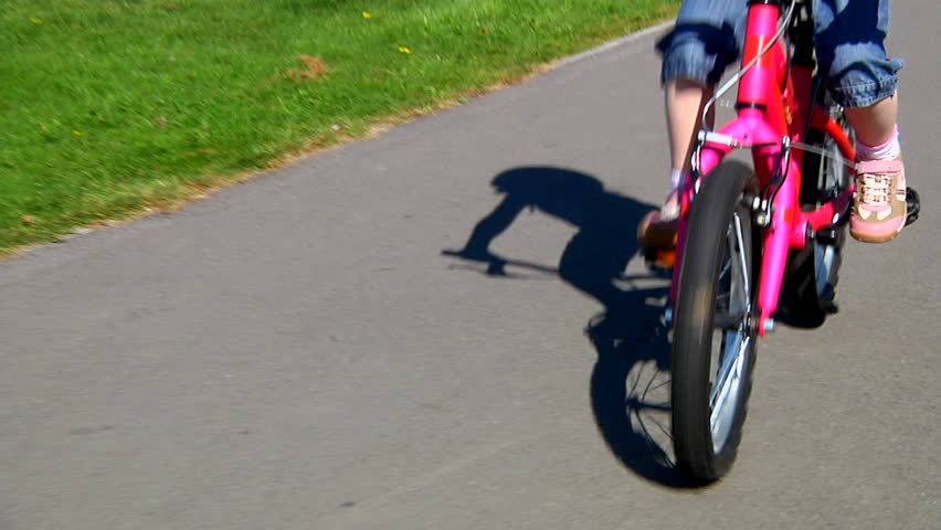 Little girl cycling in park - track along with her - HD stock video clip