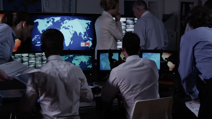 A team of security personnel working in a busy system control room, could be a weather station/airport traffic control. It could be a  power station or police/army control facility. In slow motion.