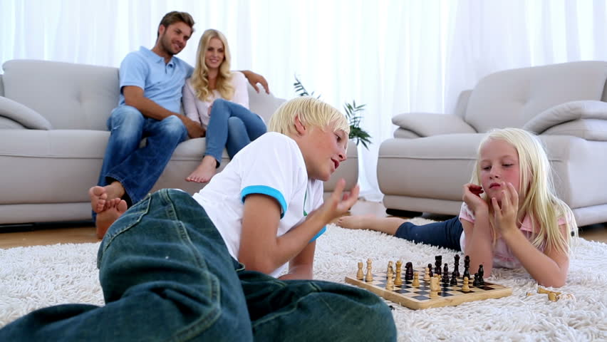 Parents Watching Their Children Play Chess On Rug Of ...