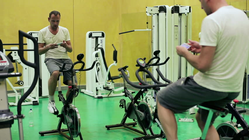 Man using smartphone during training on exercise bicycle  - HD stock footage clip