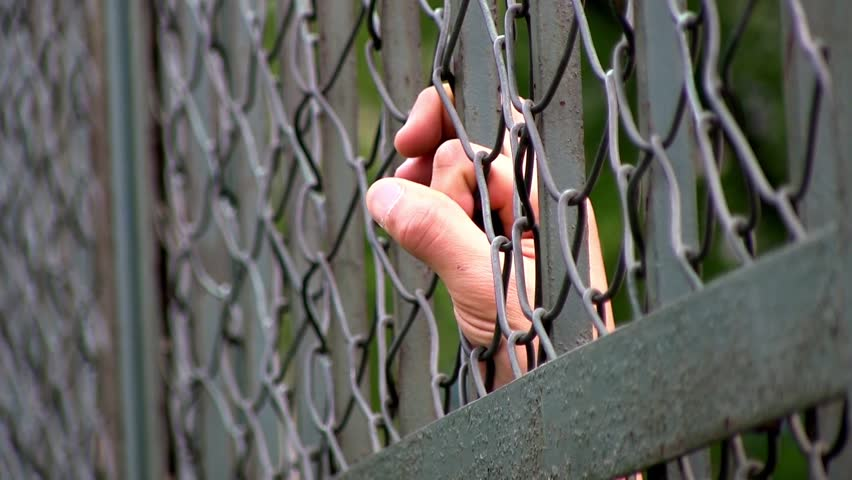 fingers through fence of prison