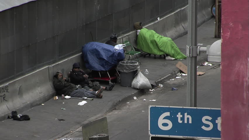 LOS ANGELES, CA - CIRCA MARCH 2012 - Skid Row in Los Angeles across from the Midnight Mission.  Homeless people sitting on the sidewalk with their belongings trying to stay warm. - HD stock video clip