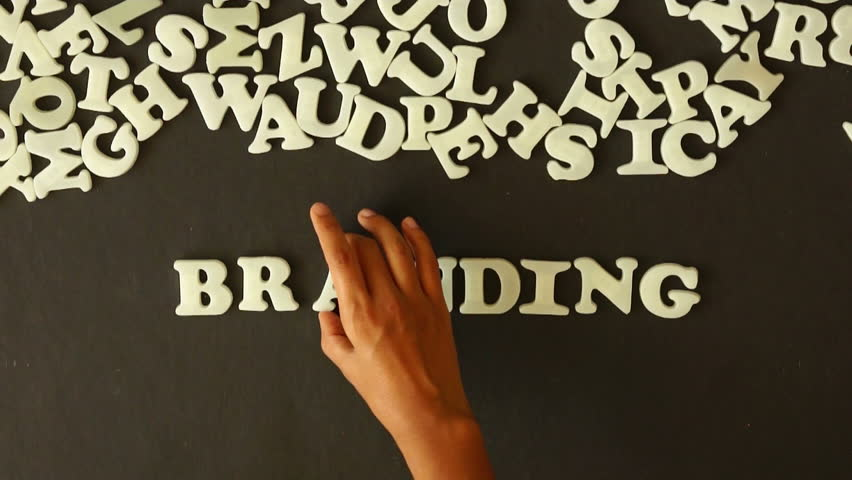 A person spelling Branding with plastic letters