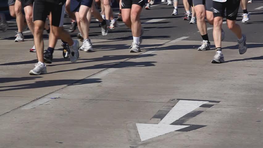 running legs of marathon participants over arrow on street - HD stock video clip