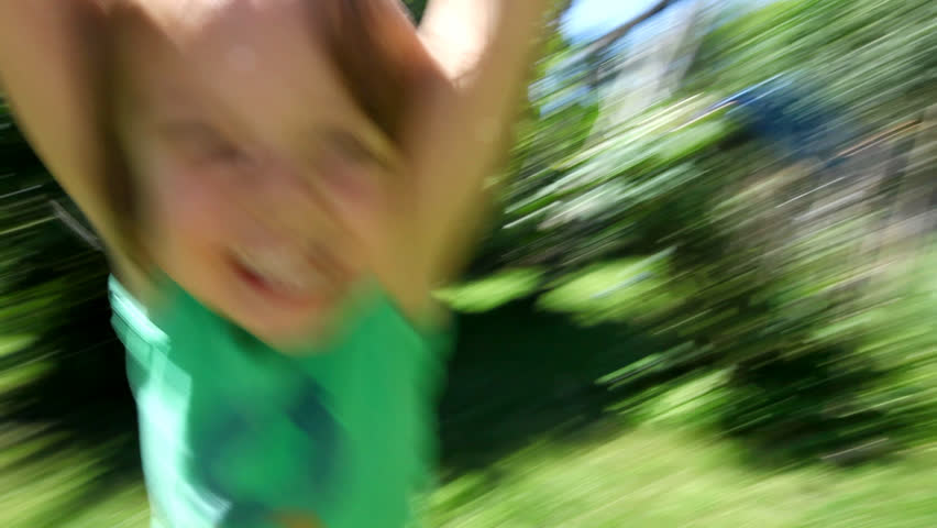 Little boy spinning around and around laughing and smiling at the end of his fathers arms on a sunny day