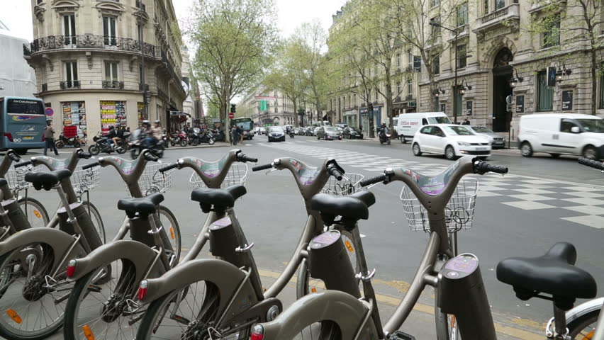 PARIS - APRIL 26: Traffic passes along Boulevard Haussmann and a Velib cycle stand on April 26, 2013 in Paris. Velib is a large scale bicycle sharing scheme in Paris - HD stock footage clip