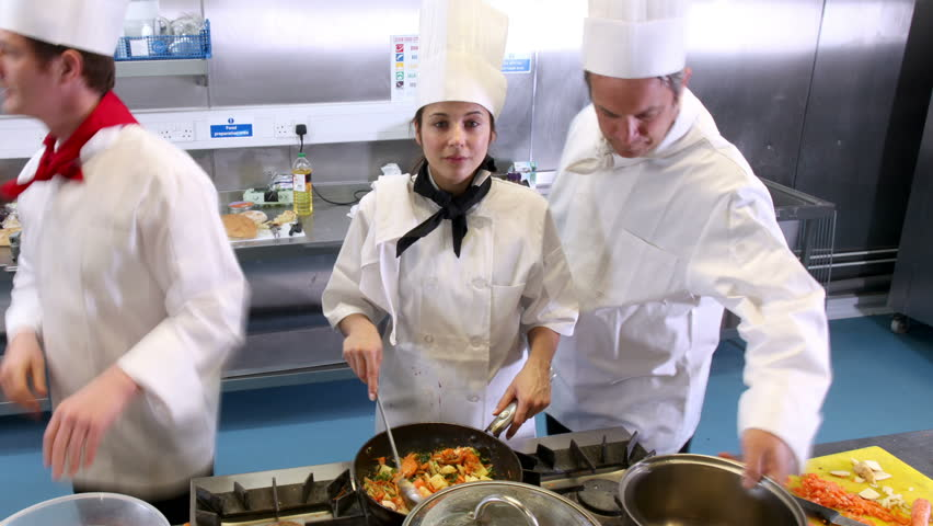 preparing food in a commercial or restaurant kitchen one female chef