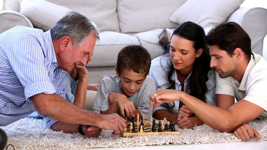 Extended family playing chess at home on the living room floor - HD stock video clip