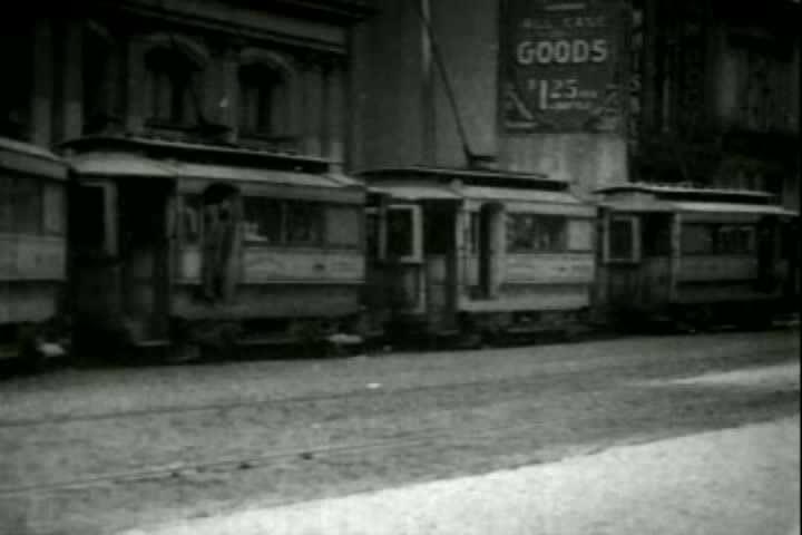 1900s - Trolleys traverse a city street in 1903.