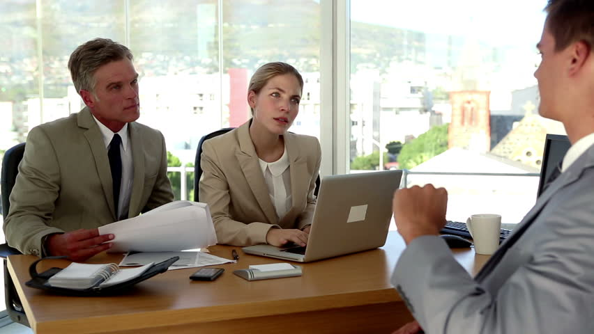 Applicant humouring the interviewers during a job interview in a bright modern office