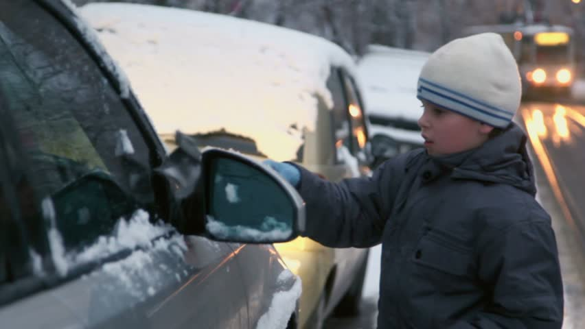 Young boy cleans car from snow at street with tram rides at evening - HD stock footage clip