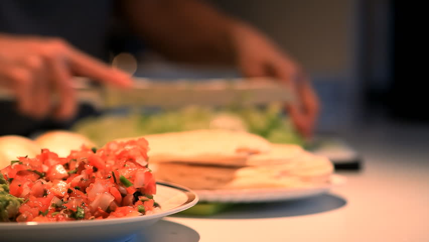 Focus on salsa and guacamole with a person out of focus in the background, preparing a Mexican meal. (Shallow DOF).