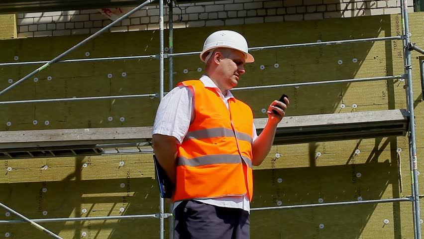 Construction Manager with folder and cell phone at the scaffolding near new building episode 1 - HD stock footage clip