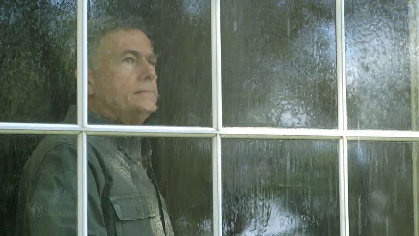 A pensive mature man watches a summer rain shower from his living room window. - HD stock video clip