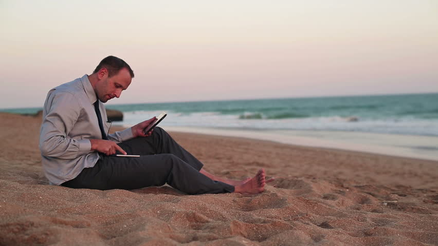 Businessman working with tablet and smartphone on the beach