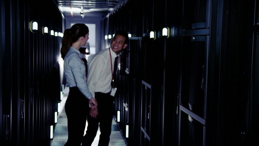 Man and woman, asian and caucasian mixed ethnicity are working in a data center with rows of server racks and supercomputers. They are checking the equipment and discussing their work.