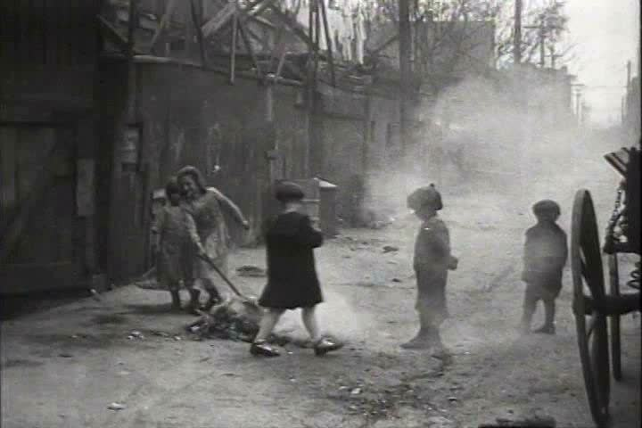 1910s, 1920s - Children play with a smoking pile of rubbish in an alley