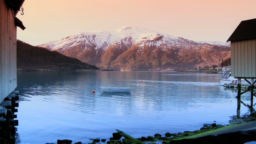 Small wooden boat anchored in clear waters of a glacial nordic fjord